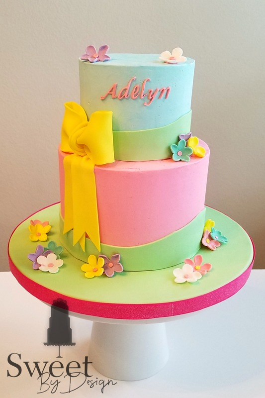 Buttercream birthday cake with fondant flowers and bow by Sweet By Design in Melissa, TX