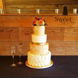 Buttercream wedding cake with fresh flower arrangement by Sweet By Design in Melissa, TX