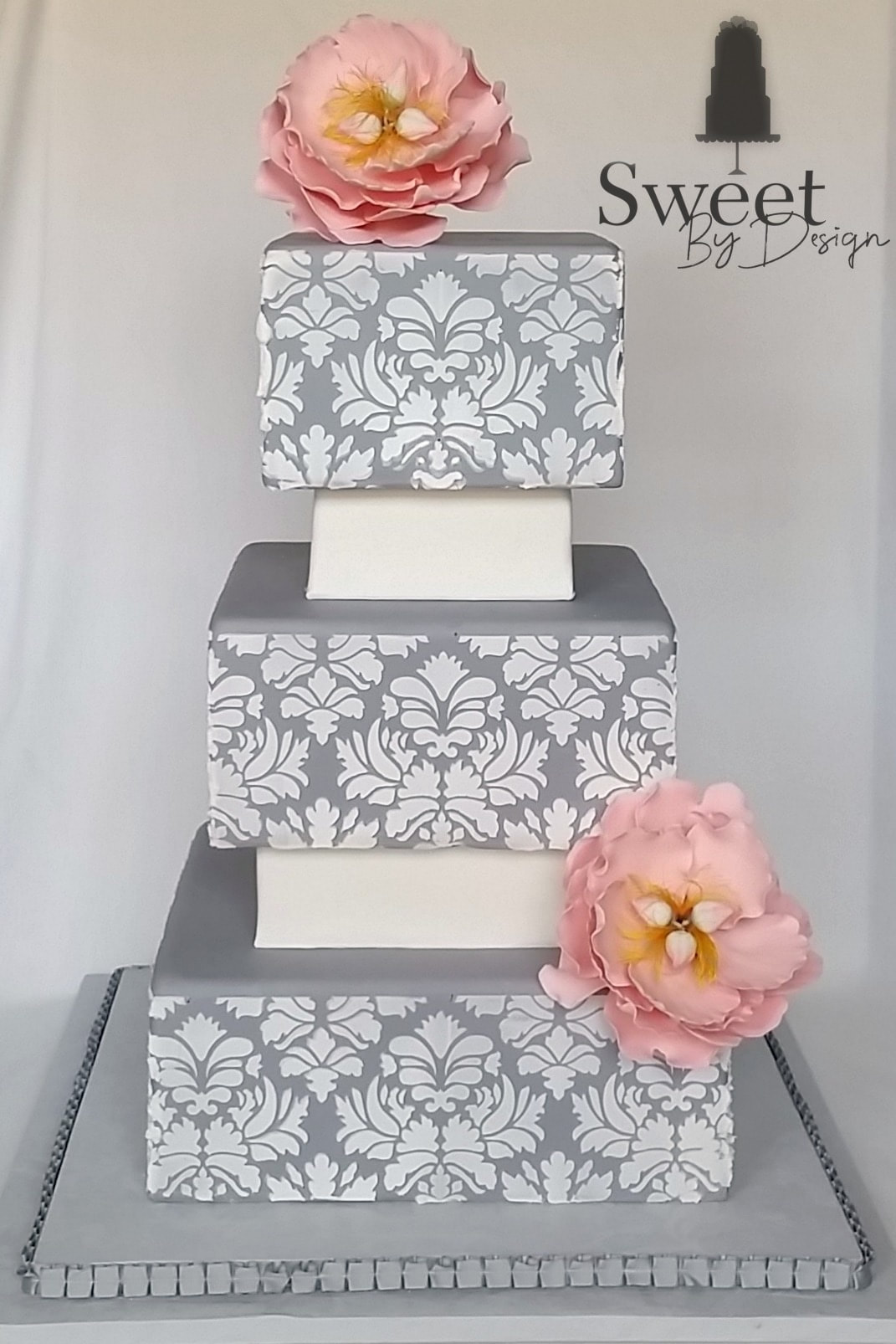 Grey and white damask wedding cake with pink fondant flowers by Sweet By Design