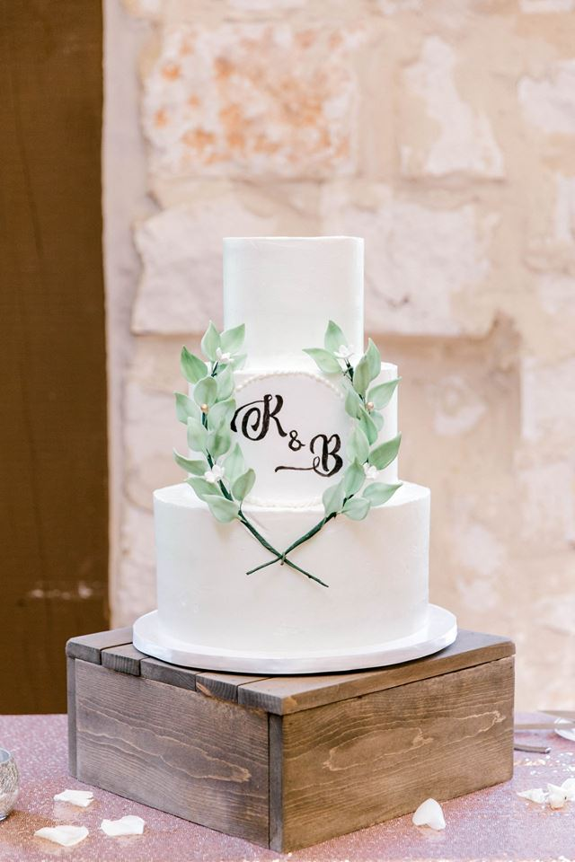 Wedding cake with greenery wreath and monogram by Sweet By Design