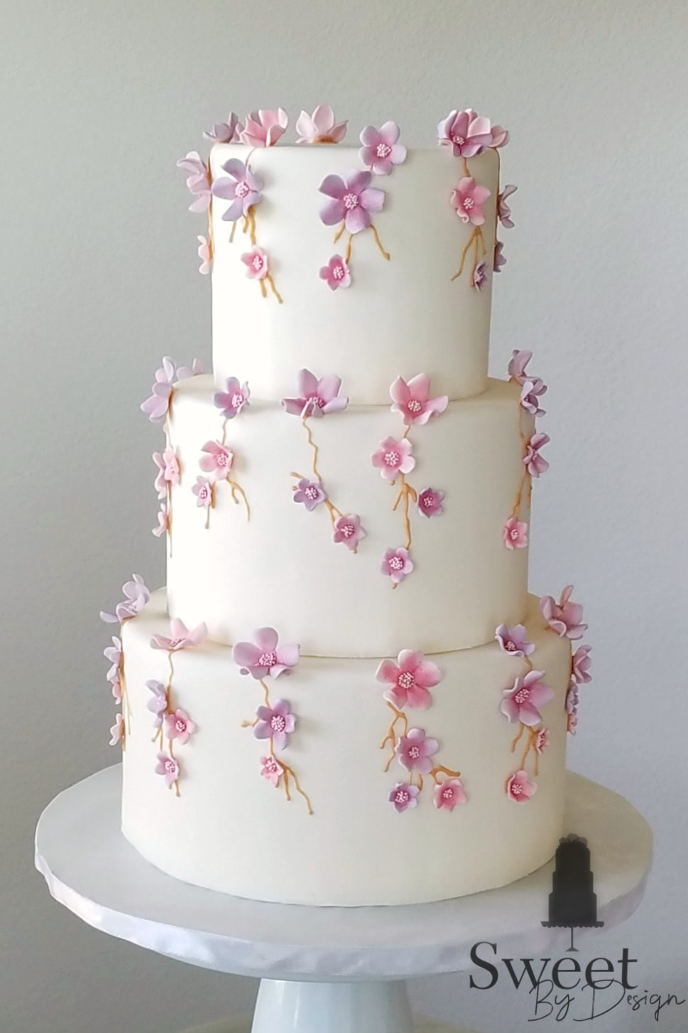 Pink and lavender flower wedding cake by Sweet By Design