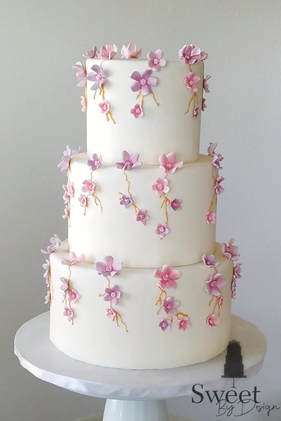 Wedding cake with pink and purple fondant flowers by Sweet By Design in Melissa, TX