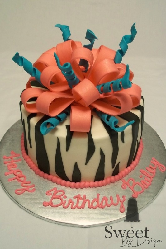 Zebra stripe birthday cake with pink and teal fondant bow by Sweet By Design in Melissa, TX